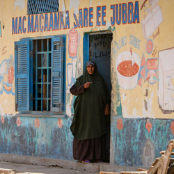 A Somali woman looks out from the doorway of a shop in Kismayo, Somalia