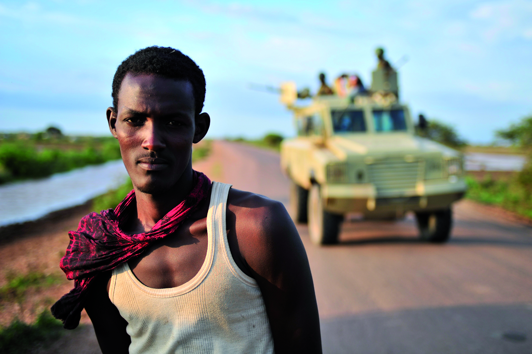 A man stands in front of an AMISOM convoy on the road connecting Afgooye to Baidoa. Previously a road controlled by Al-Shabab, AMISOM have sent forces to try and gain control of the entire stretch up to Baidoa. AU-UN IST PHOTO / TOBIN JONES.
