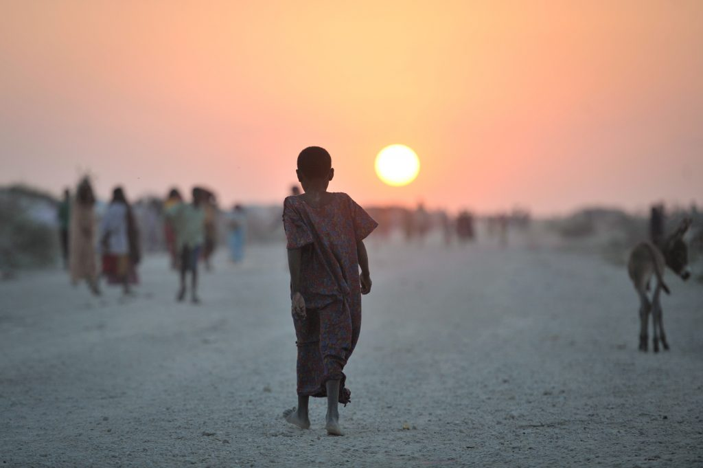 A Somali girl walks down a road at sunset in an IDP camp near the town of Jowhar on December 14. Fighting between clans has displaced more than twelve thousand people near the town of Jowhar, Somalia. Many have sought temporary shelter near an African Union military camp in the area, who are currently providing security for the IDPs. AU UN IST PHOTO / Tobin Jones.