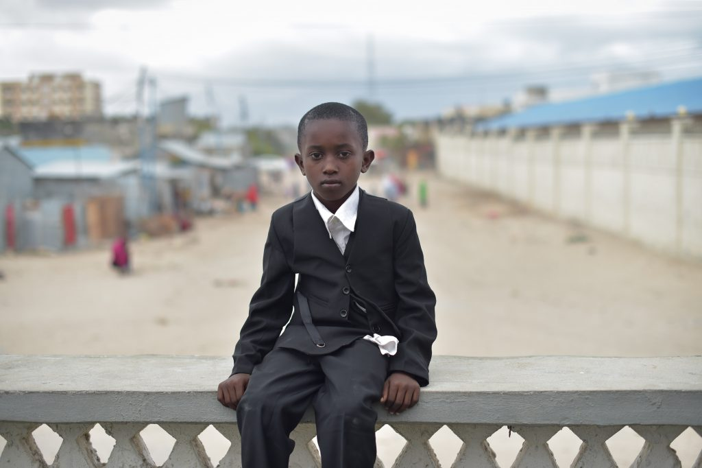 A young boy, dressed up for Eid el-Fitr, sits near the Tomb of the Unknown Soldier in Mogadishu, Somalia, on July 6, 2016. AMISOM Photo / Tobin Jones